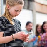 Ragazza pre teenager bullizzata con messaggio di testo su smartphone